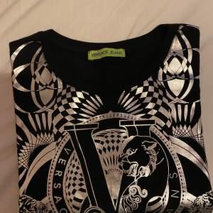 Äkta Versace jeans t shirt i storlek S.T shirten är oversize och passar super bra till ett par svarta cykelbyxor eller ett par sköna jeans. T shirten är stilren och oanvänd!