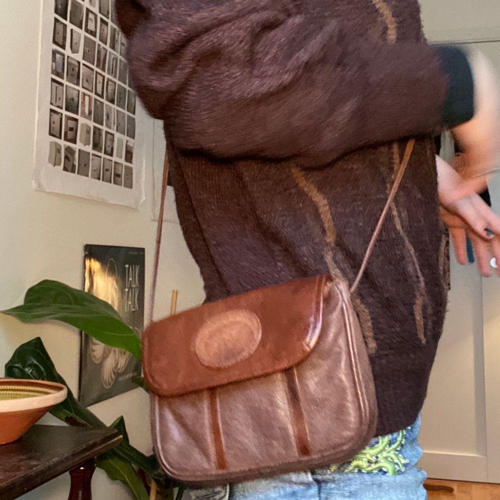 Skulle gissa att det är läderimitation! Justerbart band!!! Köpt secondhand men ändå bra skick. Frakt tillkommer på 22kr. Väskor.