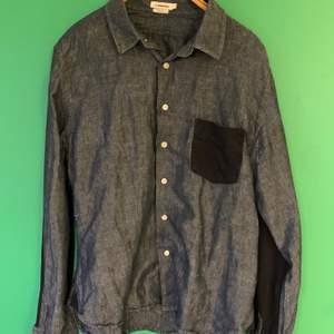 Skjorta från J. Lindeberg i denim med mörkblå detaljer på ficka och armbågar stl XL slim fit (liten i storleken).