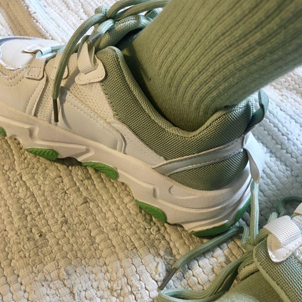 Ett par supercoola vita sneakers med gröna detaljer (minngrönt foder och snören, grön sula). Strl 38. Endast använda en gång, riktigt bra skick :). Skor.