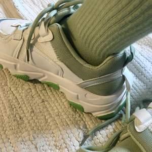 Ett par supercoola vita sneakers med gröna detaljer (minngrönt foder och snören, grön sula). Strl 38. Endast använda en gång, riktigt bra skick :)