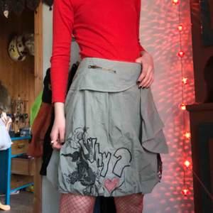 En grå-grön kjol med vackra, rejäla broderier. Kjolen har även ett spänne som man stänger/öppnar, ungefär där jag har min hand på bild 1. Kan skicka mer detaljbilder om någon är intresserad🧚🏼♀️  Möts upp i Gbg, annars står köparen för frakten xoxo