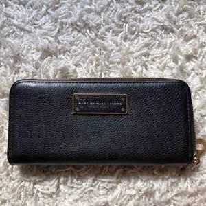 Säljer denna plånbok från Marc Jacobs, köpt på NK. Plånboken är knappt används, alltså i väldigt fint skick! Svart med gulddetaljer