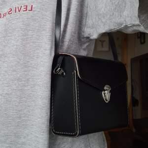 Jättecool handväska. Icke justerbara band, men jag stoppade in de i väskan så de blev kortare. Perfekt om man bara ska ha med sig de lilla som mobil,plånbok,nycklar osv. Längd:20cm, Bredd:7cm, Höjd:15cm