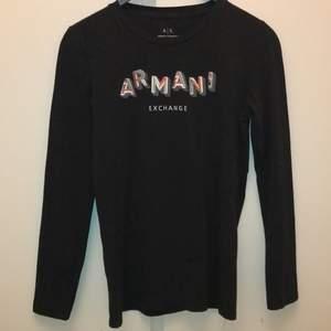 Svart långärmad tröja från Armani! Texten är delvis med paljetter också💃🏻 tröjan är i storlek M, tröjan är använd några gånger men i bra skick!!