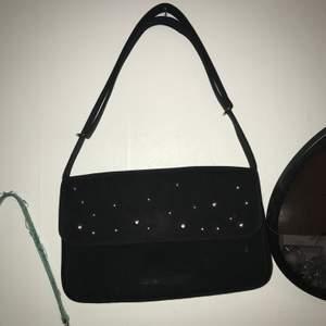 Svart handväska köpt second, den har silverdetaljer på framsidan och stängs med magnet. Den har ett par vita streck på framsidan men det märks knappt. Möta upp i Stockholm eller står köparen för frakten💞