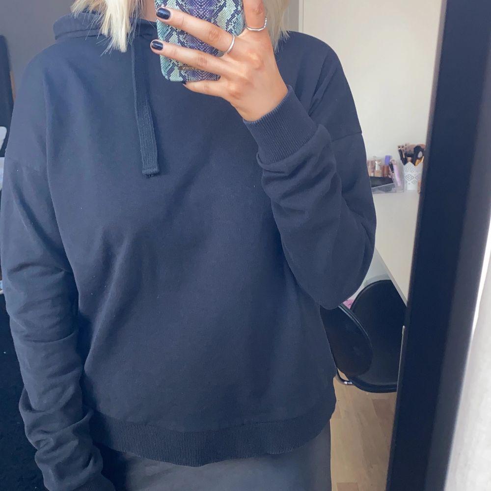 Svart hoodie med korsande rygg från NAKD i storlek S.. Huvtröjor & Träningströjor.