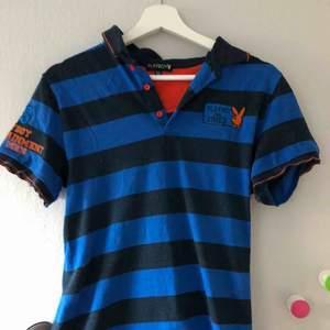playboy pike med blåa oxh mörkblåa rönder och med en sydd logga i oranget, jätte fin både på kille och tjej