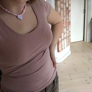 Smutsrosa urringad top som formar sig snyggt på överkroppen😋 Står strlk XS men jag är S och pga det suuuuperstretchiga materialet passar den även mig perfekt💕 Supersöt till sommaren med en kjol eller ett par kostymbyxor! GRATIS FRAKT😜