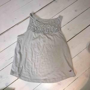Litet ljugrått linne från Hollister, spets upptill och små blommor (allt ljusgrått). Några år gammalt men inga hål, slitningar eller liknande. Väldigt gulligt, nypris ungefär 500 kr