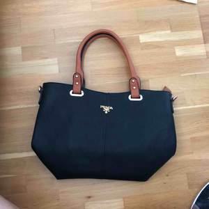 Fake Prada väska, oanvänd. Köpt i Rom. Många fickor i och en liten bakom.