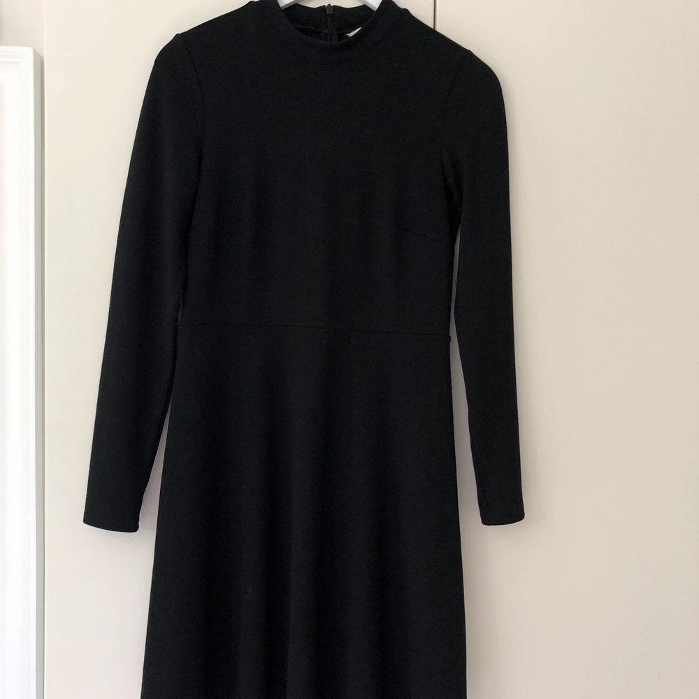 Svart basklänning från H&M, lite tjockare och väldigt stabilt material. Skuren i midjan med en aningen klockad kjol. Köparen står för frakten.. Klänningar.