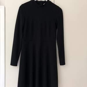Svart basklänning från H&M, lite tjockare och väldigt stabilt material. Skuren i midjan med en aningen klockad kjol. Köparen står för frakten.