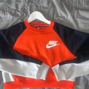Snygg och unik crop top från Nike! Orange, vit och mörkblå. Använt tre gånger så plagget är i väldigt bra skick! Skulle säga S/M i storlek. Kommer inte ihåg exakta utgångspriset men den låg runt 500kr. Säljer för 300kr Kan mötas upp eller skicka!