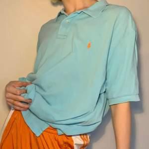 Superskön vintage turkos Ralph Lauren half button up i storleken XXL för att få en oversized siluett 🧡 Orange broderad logga på vänster bröst och två slits på vardera sida som en extra spicy detalj! Så snygg statement piece eller skön som ett mjukisplagg för extra bekvämlighet!