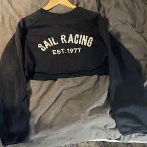 En marinblå sail racing tröja som är klippt till en croop top- se bild