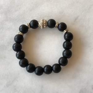 """Armband med svarta """"pärlor"""" och silver med stenar. Passar en smal vrist, kan mäta om så önskas. Öppnas och stängs med magneter. Kan skickas mot frakt"""