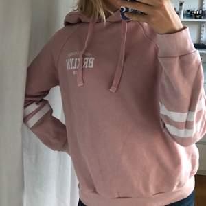 """Rosa hoodie ifrån Ginatricot. Jättefina vita detaljer och skönt material. Den är tvättad flera gånger vilket har gjort att de vita ränderna har lite """"sprickor"""" men det är inget som märks."""