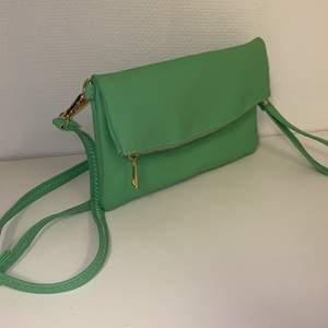 """Handväska som kan användas på två sätt. Med lång rem eller som clutch med """"handledsrem"""". Fräsch grön färg. Dragkedja och magnet som stängning. Flera fack inuti varav ett med dragkedja och ett på baksidan med dragkedja. Nästan nyskick, aldrig använd!"""