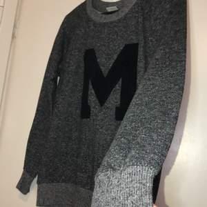 En grå tjocktröja med ett stort M på. Säljs för 60kr + frakt eller mötas upp i Malmö💗