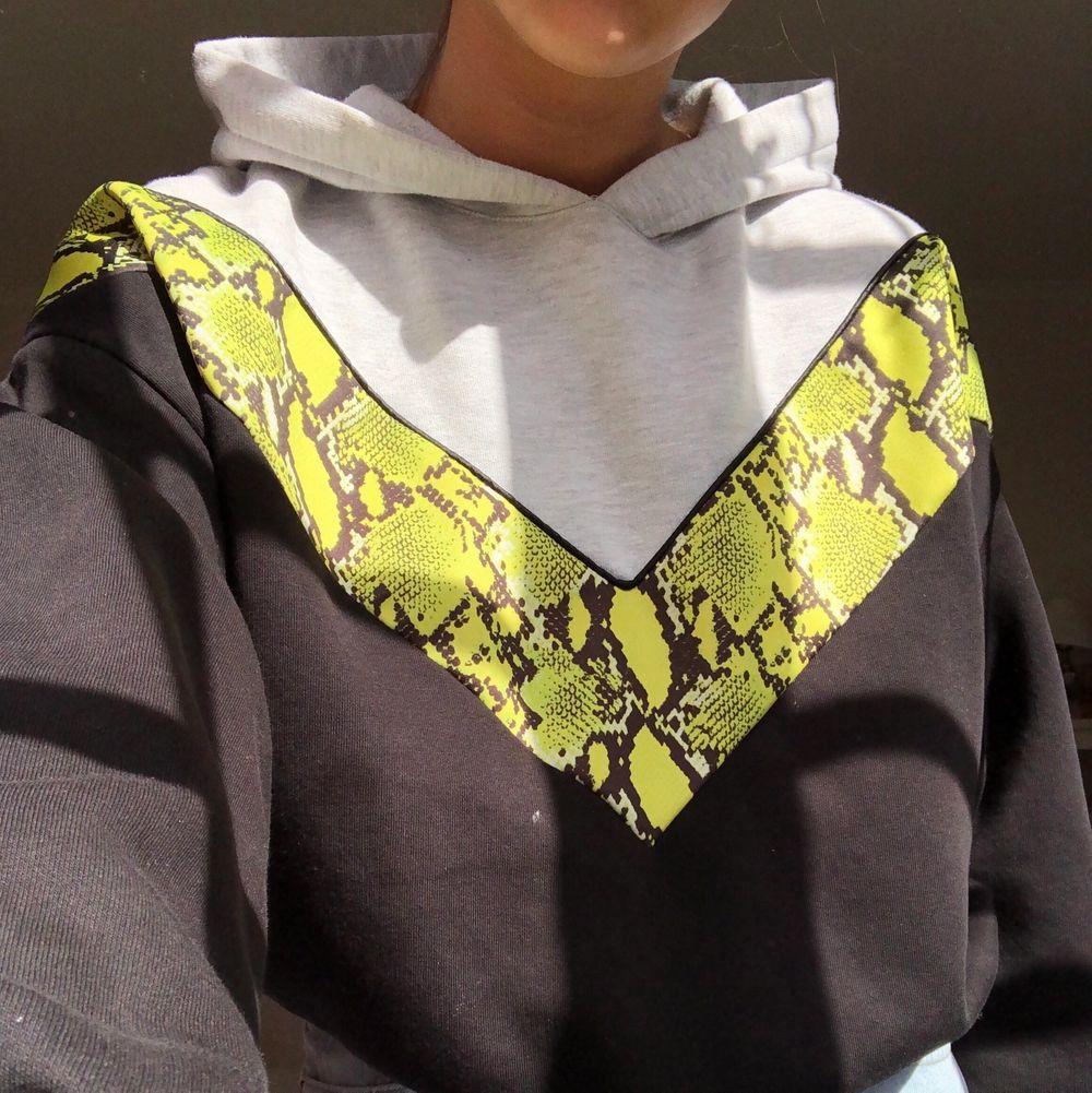 Supercool svart och grå hoodie med neon grön/gul ormskins detalj! Typ croppad med snörning där nere så man kan stylea den lite som man vill. Köpare står för frakt! Högsta bud 200. Huvtröjor & Träningströjor.