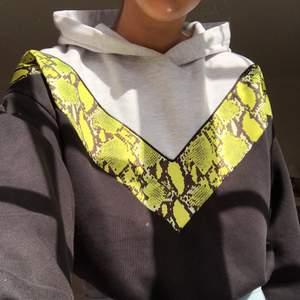 Supercool svart och grå hoodie med neon grön/gul ormskins detalj! Typ croppad med snörning där nere så man kan stylea den lite som man vill. Köpare står för frakt! Högsta bud 200