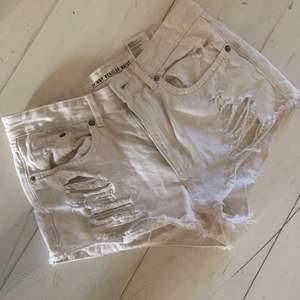 Xs vita shorts med slitningar