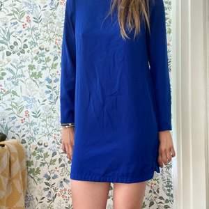 En härligt blå klänning. Snyggt att knyta ett band i midjan. Den är kort i modellen dock är jag 179cm lång. Skicket är okej därav priset.