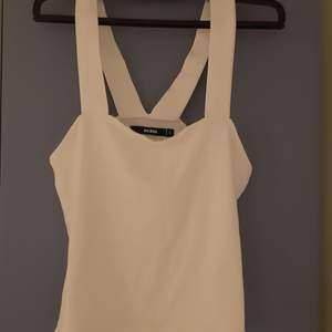 Ett vitt linne med tjocka band som möts i ryggen. Knappt använt.