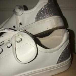 Snygga vita sneakers med silver/glitter detaljer bak på skon✨ Använda en del men i bra skick. Skriv privat vid intresse💕💕 Ganska lågt pris då jag it e kommer ihåg vad de kostade. Köparen står för frakten🤩 (priset kan diskuteras vid snabba köp)