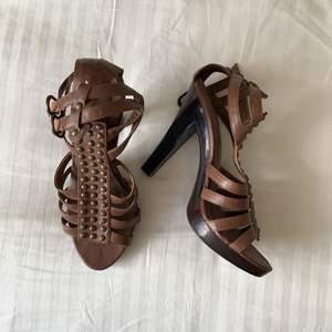 Bruna gladiatorliknande sandaletter i storlek 38. Klackhöjd: 12cm. Aldrig använda men har stått i garderoben i säkert 10år, kan inte se något märke på skorna så vet inte vart de är ifrån.
