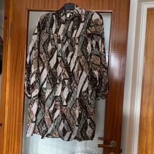 Mönstrad klänning i strl. 44. Pris exkl. frakt, köparen står för frakten.