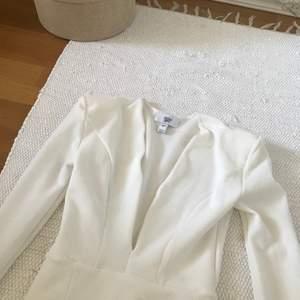 Oanvänd Rebecca Stella vit klänning med axelkuddar. Perfekt som studentklänning och skolavslutningsklänning. Strl XS