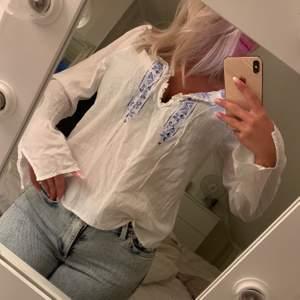 Säljer denna vita blusen med mörkblå brodering vid brösten. Man kan både välja att ha den öppen eller knyta den så att den blir stängd vid brösten. Säljs för 60 kr. Köparen står för frakten!