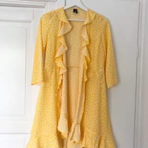 Gul omlottklänning med vita prickar från Vero Moda. Volang nedtill. Aldrig använd! Mycket fint skick. Stl S, true to size. Köparen står för frakten 44 kr
