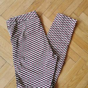 Tighta, mönstrade byxor från H&M. Dragkedja och knapp i sidan. Fejk-ficka bak. Snyggt mönster i rött, svart och ljusbeige.