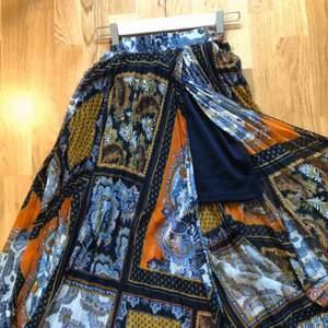 Lång flowig kjol i härligt boho mönster. Stretch i midjan och mörkblp underkjol. Har tre lagningar på midjebandet (bild 3) men de syns ej eftersom mönstret smälter in. Säljs pga för liten