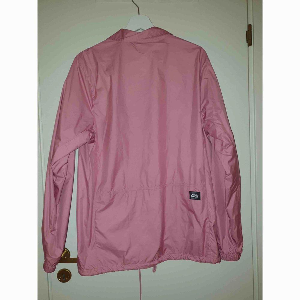 Coach jacket från Nike. Rosa i storlek M, knappt använd därav väldigt fint skick. Rak i modellen, två fickor nedtill med knappar. Köparen betalar frakten.  . Jackor.
