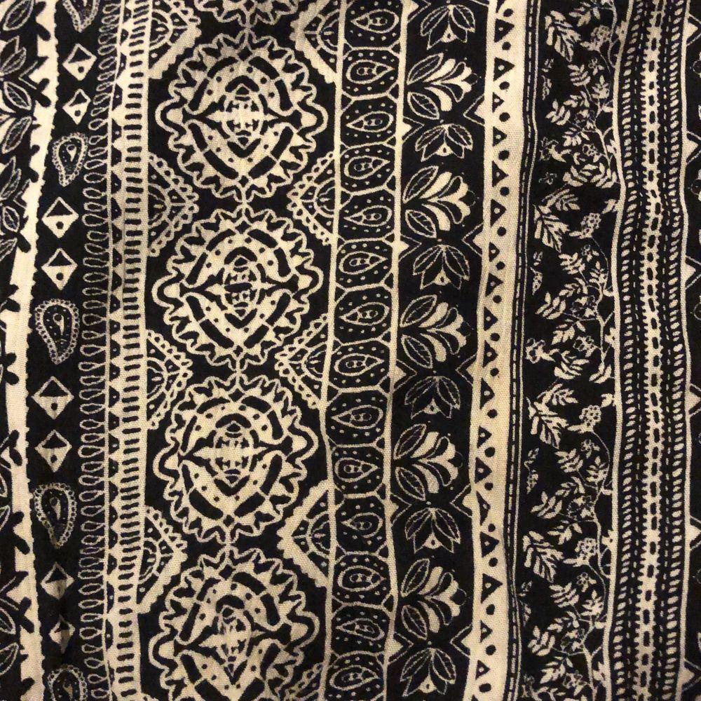 Ett luftigt svart & vitt linne med mönster på, två band korsar varandra bak i ryggen (bild 2). Säljer då jag inte använt det på länge. Toppar.