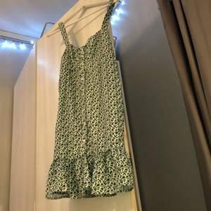 En somrig och blommig grön och vit klänning i stl S