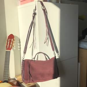 Äkta läder väska från Zara i fin lila/vinröd färg! Använd fåtal gånger och säljs på grund av ingen användning. I väldigt fin skick, inga repor bara en liten missfärgning framme som syns knappt.