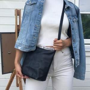 snygg och stilren väska i svart äkta läder, justerbar axelband, fler fack innuti inklusive en korthållare. använd men alla dragkedjor fungerar som de ska!