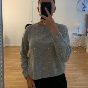En grå stickad tröja med väldigt fina detaljer i form av pärlor, tröjan kommer tyvärr inte till användning längre