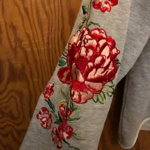Grå hoodie med broderade blommor på ärmarna och på luvan! Supersöt. Lite cropped där fram.