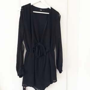 En svart, v-ringad jumpsuit med öppna ärmar. Använd men i bra skick 🖤