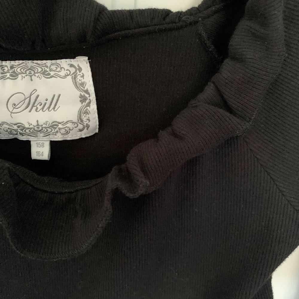 En svart långärmad off shoulder tröja som är ribbad, alltså små ränder på (se bild 3), och har små volanger runt. Storlek 158/164 som är S. Använd 1-2 gånger så den är i bra skick. Säljer för 85 kr + frakt 🖤. Tröjor & Koftor.