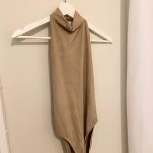 Beige mockabody från Nelly i storlek Small. Köptes för 350kr, säljer för 120kr. Helt öppen i ryggen och täckande fram.