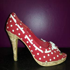 Röda klackskor från Vox Shoes med vita prickar. Endast använda 1 gång. Säljes på grund av att de inte är rätt storlek för mig. Storlek: 40 Klackhöjd: 12 cm. Klackarna har slitage på baksidan (se bild 3).