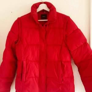 Röd dunjacka med avtagbara ärmar