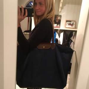 Säljer min longchamp väska i stort format som är perfekt för dig som är på kortare resor. Som en overnight/ weekend bag. Den är marinblå med en innerficka och bruna handtag.  Finns i Eskilstuna.